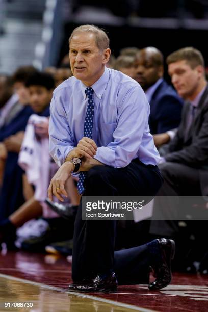 Michigan Wolverine head coach John Beilein kneels while watching the offensive during an college basketball game between Michigan Wolverines and the...