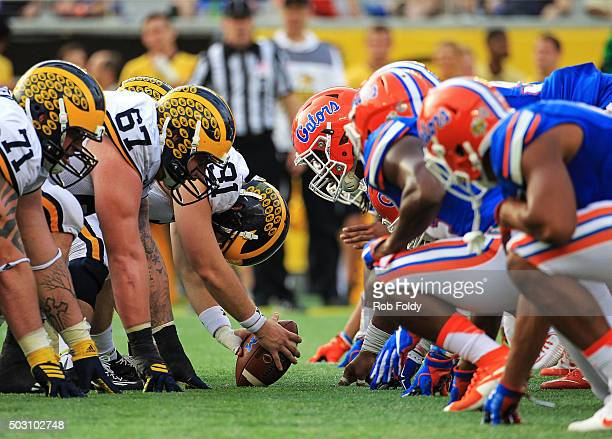 Michigan Wolverines and Florida Gators players line up before a snap during the second half of the Buffalo Wild Wings Citrus Bowl game at Orlando...