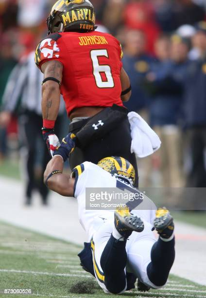Michigan Wolverines defensive back Khaleke Hudson grabs Maryland Terrapins running back Ty Johnson by his pants during a college football game...