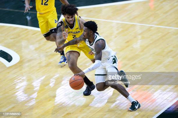 Michigan Wolverines forward Isaiah Livers hounds Michigan State Spartans guard Rocket Watts beyond the three-point line during a college basketball...