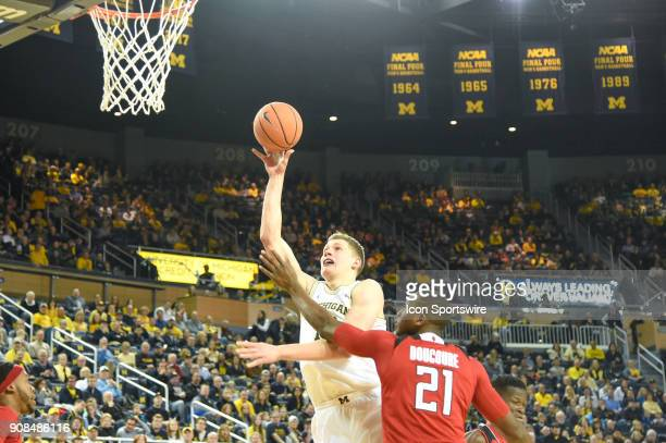Michigan Wolverines forward Moritz Wagner drives in for a layup past Rutgers Scarlet Knights forward Mamadou Doucoure during the Michigan Wolverines...