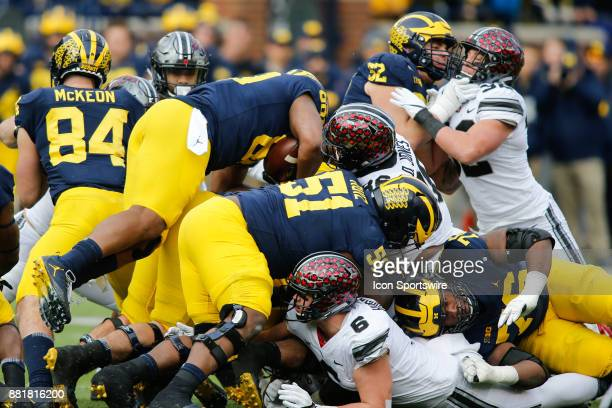 Michigan Wolverines full back Khalid Hill dives over a pile of bodies for extra yards during game action between the Ohio State Buckeyes and the...