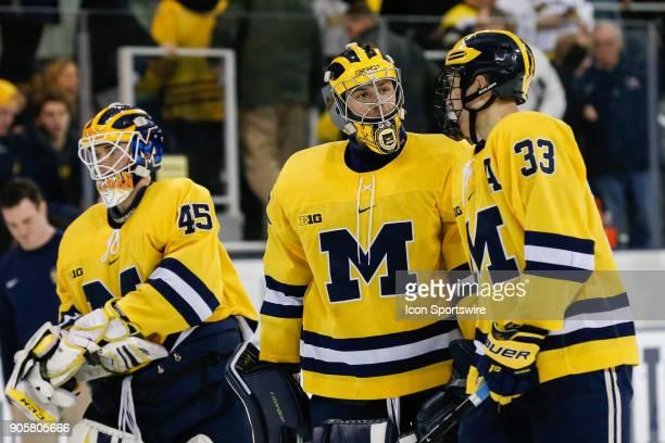 Michigan Wolverines goalie Hayden Lavigne talks to Michigan Wolverines defenseman Joseph Cecconi as they head for the locker room during intermission...