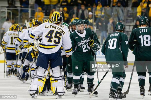 Michigan Wolverines goalie Jack LaFontaine shakes hands with Michigan State Spartans forward Jake Smith at the conclusion of a regular season Big 10...