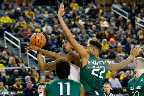 Michigan Wolverines guard Charles Matthews shoots over Jacksonville Dolphins center Radwan Bakkali during the first half of a regular season...
