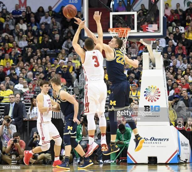 Michigan Wolverines guard Duncan Robinson blocks a second half shot by Wisconsin Badgers guard Zak Showalter in the Big 10 Tournament Championship...