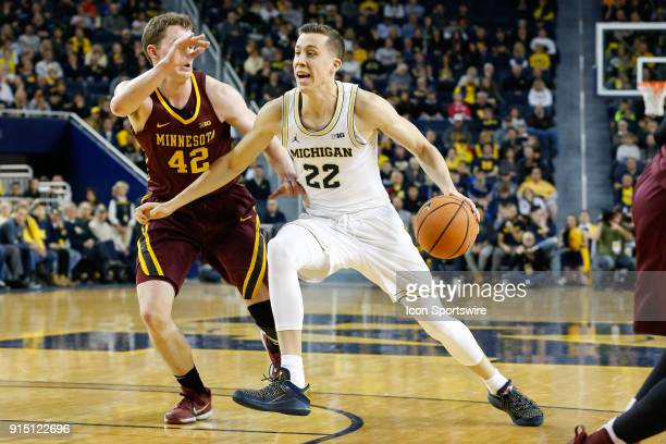 Michigan Wolverines guard Duncan Robinson drives to the basket against Minnesota Golden Gophers forward Michael Hurt during a regular season Big 10...