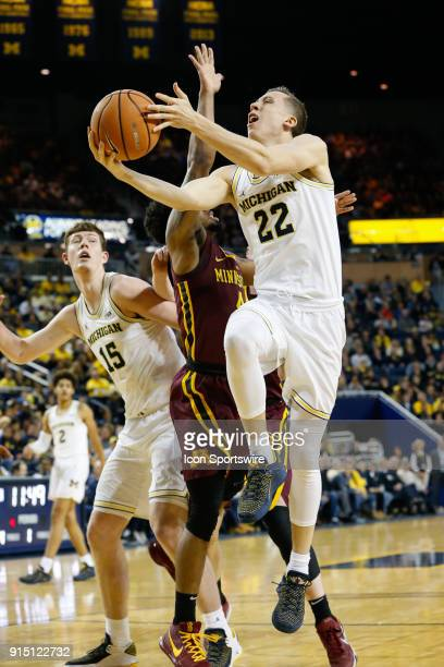 Michigan Wolverines guard Duncan Robinson goes in for a layup against Minnesota Golden Gophers forward Michael Hurt during a regular season Big 10...