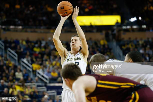 Michigan Wolverines guard Duncan Robinson shoots a free throw during a regular season Big 10 Conference basketball game between the Minnesota Golden...