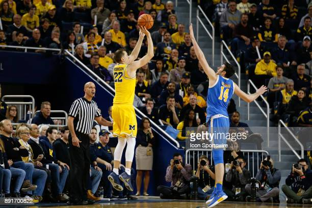 Michigan Wolverines guard Duncan Robinson shoots a jump shot over UCLA Bruins forward Gyorgy Goloman during a regular season non-conference...