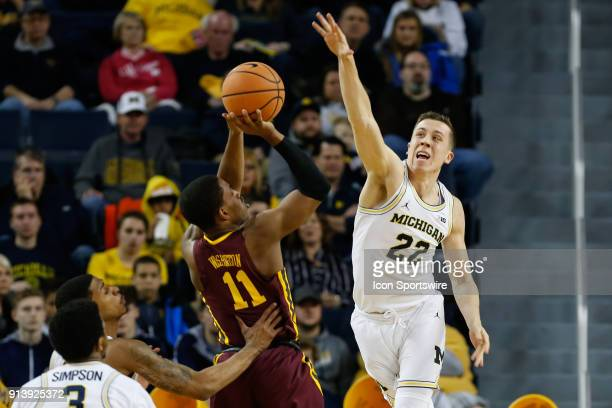 Michigan Wolverines guard Duncan Robinson tries to block a shot by Minnesota Golden Gophers guard Isaiah Washington during the first half of a...
