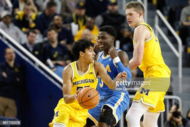 Michigan Wolverines guard Eli Brooks drives to the basket against UCLA Bruins guard Aaron Holiday during a regular season nonconference basketball...