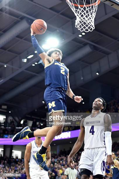 Michigan Wolverines guard Jordan Poole dunks against Northwestern Wildcats forward Vic Law on December 4 2018 at the WelshRyan Arena in Evanston...