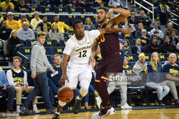 Michigan Wolverines guard MuhammadAli AbdurRahkman drives past Central Michigan Chippewas guard Kevin McKay during the Michigan Wolverines game...