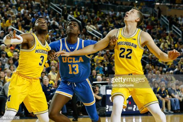 Michigan Wolverines guard Zavier Simpson and Michigan Wolverines guard Duncan Robinson battle for rebounding position against UCLA Bruins guard Kris...