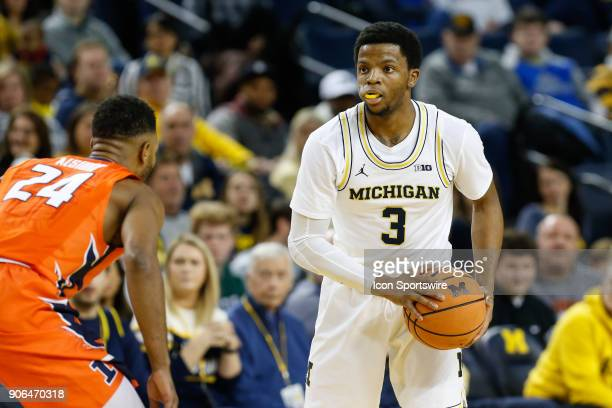 Michigan Wolverines guard Zavier Simpson looks to pass the ball during a regular season Big 10 Conference basketball game between the Illinois...