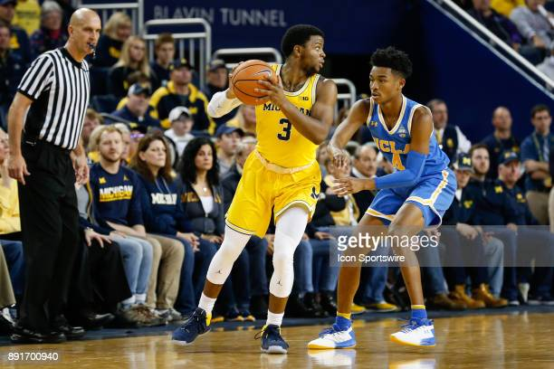 Michigan Wolverines guard Zavier Simpson looks to pass the ball while being defended by UCLA Bruins guard Jaylen Hands during a regular season...