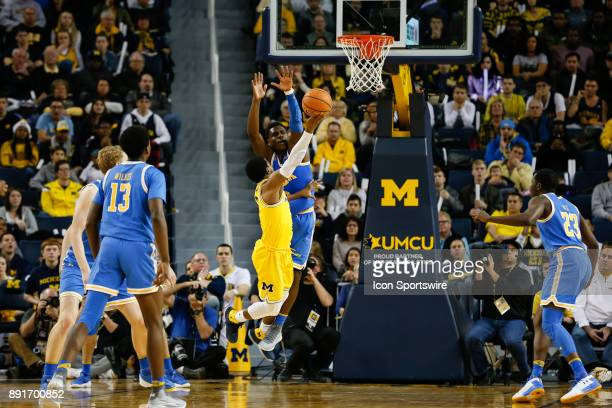 Michigan Wolverines guard Zavier Simpson shoots over UCLA Bruins guard Aaron Holiday during a regular season nonconference basketball game between...