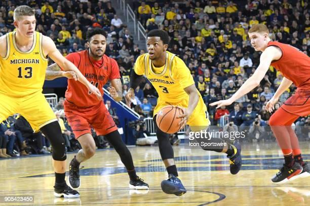 Michigan Wolverines guard Zavier Simpson splits the defense of Maryland Terrapins guard Jared Nickens and Maryland Terrapins guard Kevin Huerter...