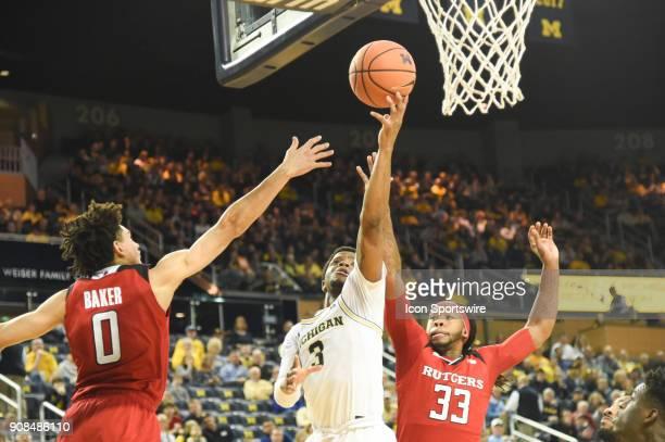 Michigan Wolverines guard Zavier Simpson splits the defense of Rutgers Scarlet Knights guard Geo Baker and Rutgers Scarlet Knights forward Deshawn...
