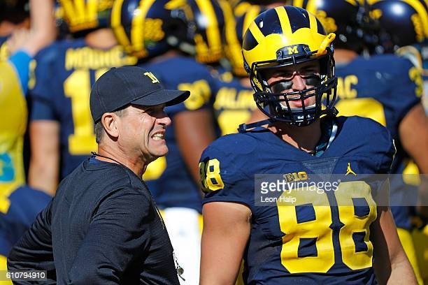 Michigan Wolverines head coach Jim Harbaugh talks with Jake Butt of the Michigan Wolverines during the first quarter of the game against the Penn...