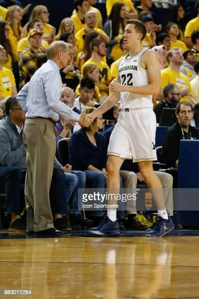 Michigan Wolverines head coach John Beilein shakes hands with Michigan Wolverines guard Duncan Robinson as he leaves the game during a regular season...