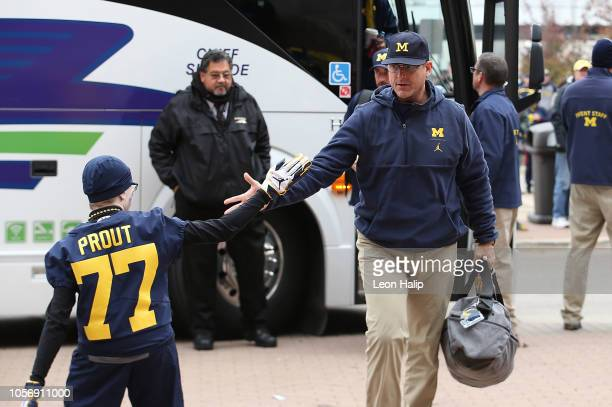 Michigan Wolverines Head football coach Jim Harbaugh walks off the bus prior to the start of the game against the Penn State Nittany Lions at...