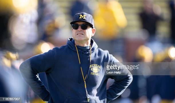 Michigan Wolverines head football coach Jim Harbaugh watches the pregame warm ups prior to the start of the game against the Michigan State Spartans...