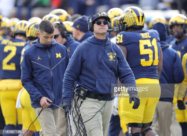 Michigan Wolverines Head Football Coach Jim Harbaugh watches the replay during the fourth quarter of the game against the Michigan State Spartans at...