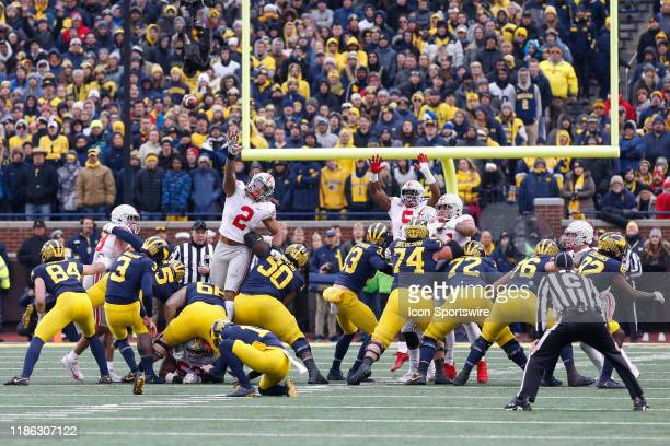 Michigan Wolverines kicker Quinn Nordin kicks a field goal while Ohio State Buckeyes defensive end Chase Young and Ohio State Buckeyes linebacker...