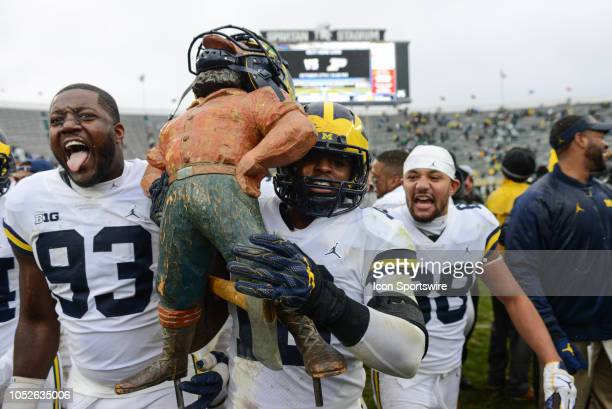 Michigan Wolverines linebacker Devin Bush and nose tackle Lawrence Marshall walk off the field with the Paul Bunyan trophy following a Big Ten...