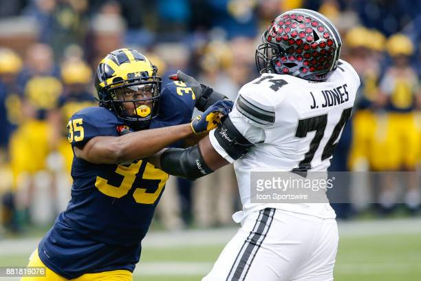 Michigan Wolverines linebacker Josh Uche fight through a block by Ohio State Buckeyes offensive lineman Jamarco Jones during game action between the...