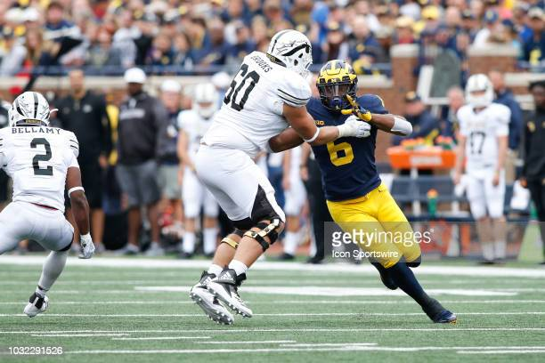 Michigan Wolverines linebacker Josh Uche fights off a block by Western Michigan Broncos offensive lineman Mark Brooks during game action between...