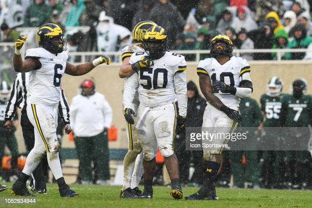 Michigan Wolverines nose tackle Michael Dwumfour and linebacker Devin Bush celebrate a late tackle during a Big Ten Conference college football game...