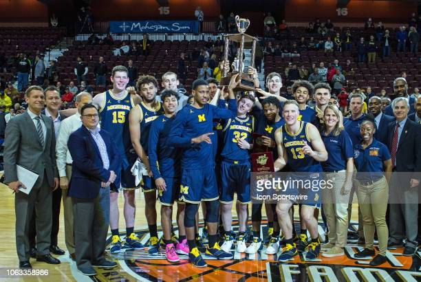 Michigan Wolverines players and staff pose with the championship trophy after defeating Providence on November 18 at Mohegan Sun Arena in Uncasville...