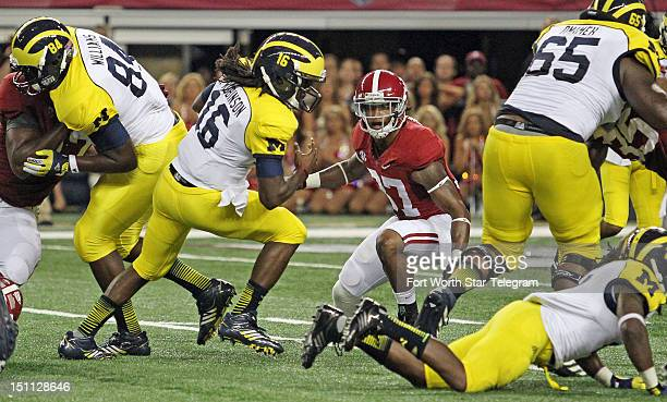Michigan Wolverines quarterback Denard Robinson keeps the ball and drives for a first down against Alabama late in the second quarter of the Cowboys...
