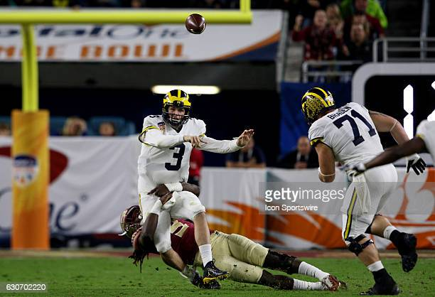 Michigan Wolverines quarterback Wilton Speight manages to make the throw while being tackled by Florida State Seminoles defensive end Josh Sweat...