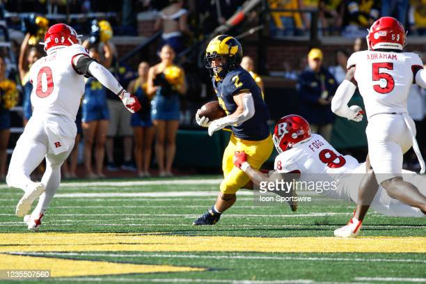 Michigan Wolverines running back Blake Corum carries the ball while Rutgers Scarlet Knights linebacker Tyshon Fogg tries to make a tackle as Rutgers...