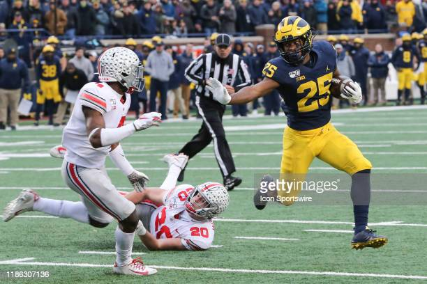 Michigan Wolverines running back Hassan Haskins runs with the ball while trying to avoid being tackled by Ohio State Buckeyes safety Jordan Fuller...