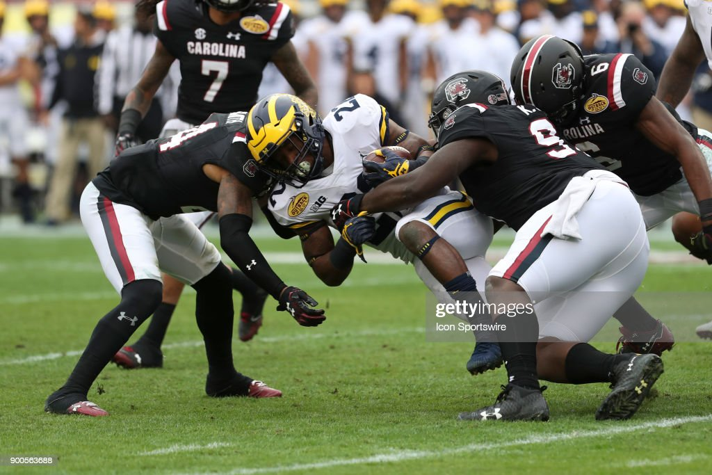 Michigan Wolverines running back Karan Higdon (22) is tackled by South Carolina Gamecocks defensive back D.J. Smith (24) and South Carolina Gamecocks defensive lineman Kobe Smith (97) during the 2018 Outback Bowl between the Michigan Wolverines and South Carolina Gamecocks on January 01, 2018 at Raymond James Stadium in Tampa, FL.