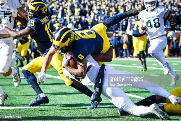 Michigan Wolverines wide receiver Ronnie Bell catches a pass and runs for a short gain as hes upended by Michigan State Spartans cornerback Josiah...