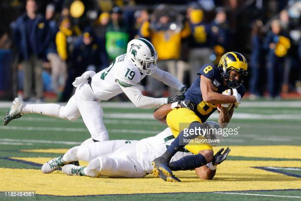 Michigan Wolverines wide receiver Ronnie Bell is tackled by Michigan State Spartans corner back Josh Butler and Michigan State Spartans linebacker...