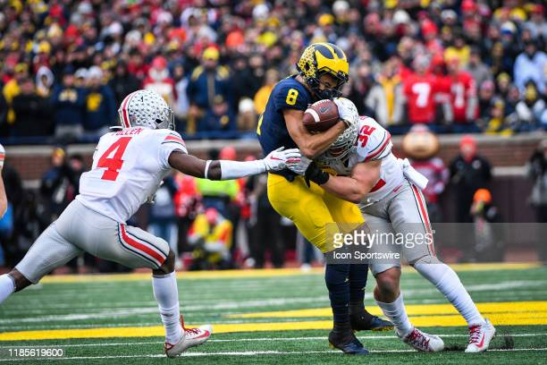 Michigan Wolverines wide receiver Ronnie Bell makes a catch over the middle and is hit hard by Ohio State Buckeyes linebacker Tuf Borland during the...