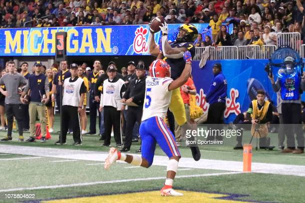 Michigan Wolverines wide receiver Tarik Black leaps over Florida Gators defensive back CJ Henderson during the Peach Bowl between the Florida Gators...