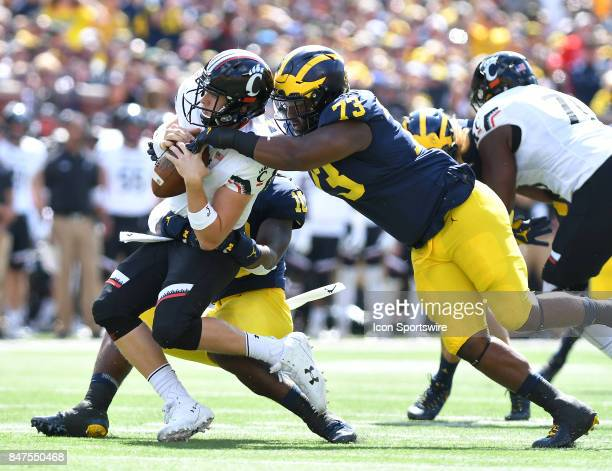 Michigan's Devn Bush left and Maurice Hurst team up to sack Cincinnati quarterback Hayden Moore during a college football game between the Cincinnati...
