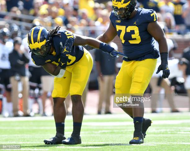 Michigan's Devn Bush left takes a bow after he and Maurice Hurst right teamed up to sack Cincinnati quarterback Hayden Moore during a college...