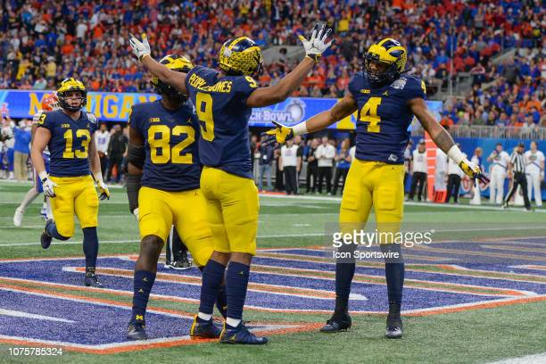 Michigans Donovan PeoplesJones celebrates with Nico Collins after catching a touchdown pass during the first half of the ChickfilA Peach Bowl between...