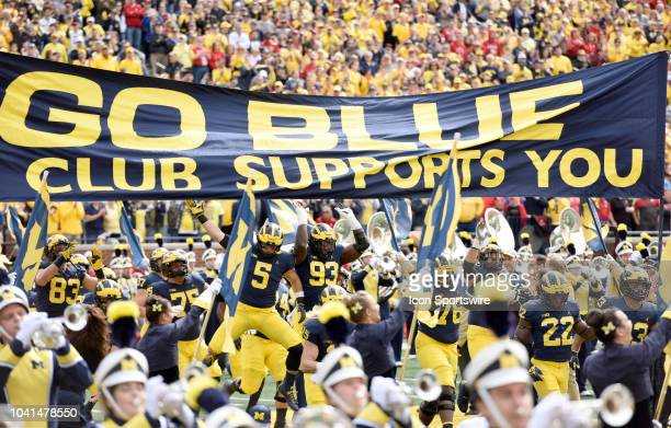 Michigan's football team jumps up to touch the M Go Blue Club banner at midfield before their 56-10 win over the Nebraska Cornhuskers in a college...
