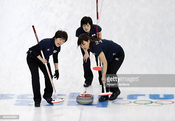 Michiko Tomabechi and Chinami Yoshida of Japan sweep the ice as Ayumi Ogasawara looks on during Curling Women's Round Robin match between Japan and...
