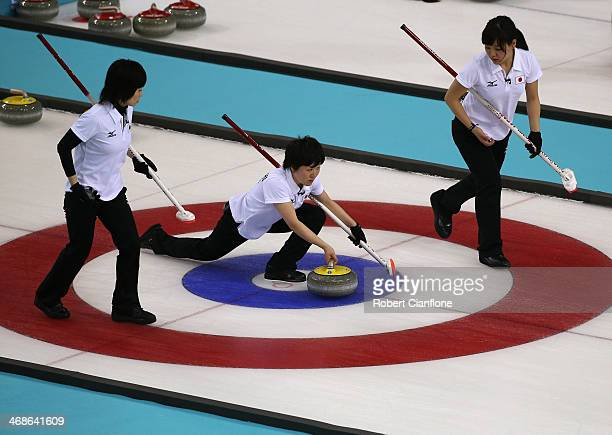 Michiko Tomabechi of Japan delivers the stone while Yumie Funayama and Chinami Yoshida prepare to sweep during the Curling Women's Round Robin match...